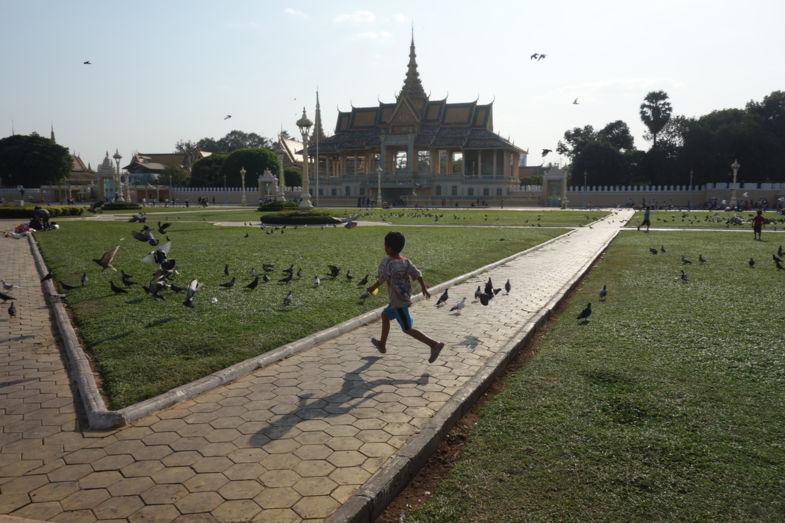 Vliegend en spelend kind in lijn met de vogels in Phnom Penh