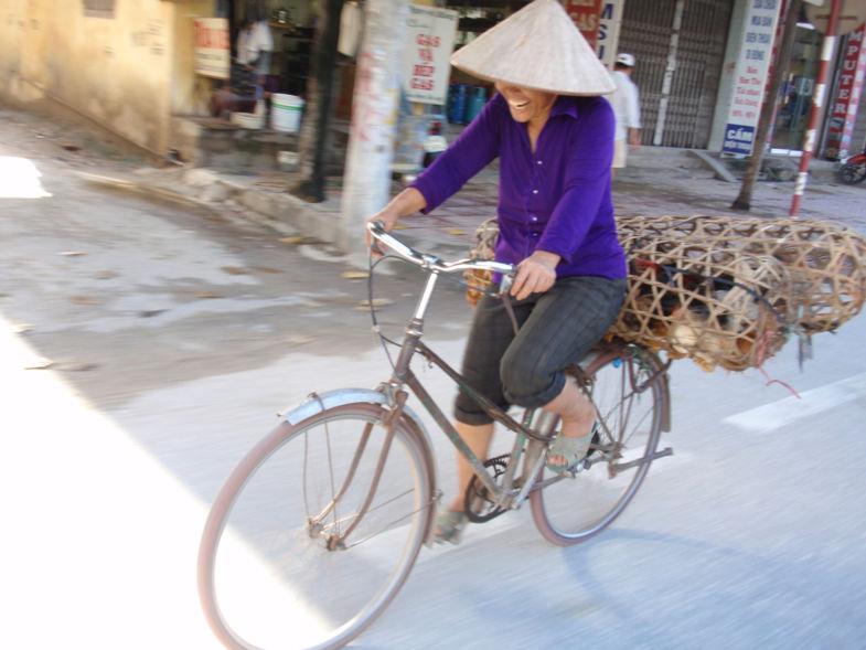 Schaterende lach van Vietnamese vrouw op de fiets met kippen achterop.