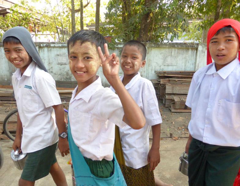 Schooljongens met rijst pannetje. In Yangon.