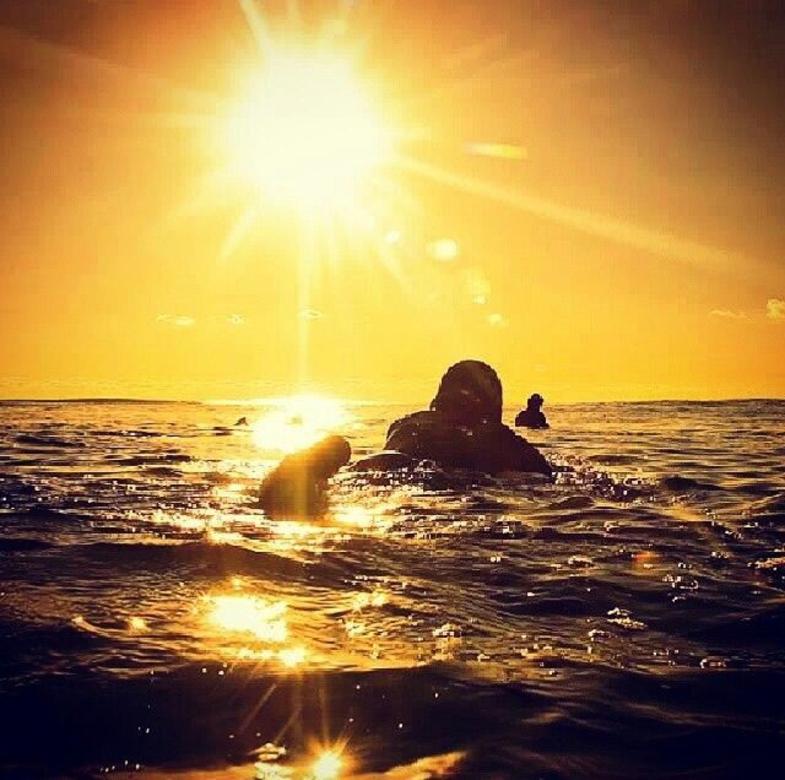 Een surfer wacht op een golf in de branding van Uluwatu.
