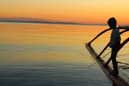 Vissend jongetje tijdens geweldige zonsondergang