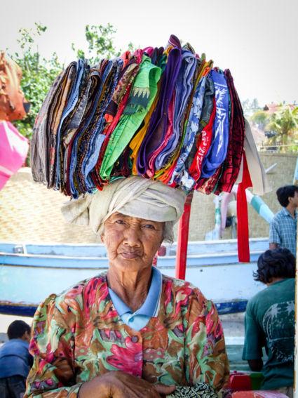 Lieve Balinese oude vrouw verkoopt batik-doeken.