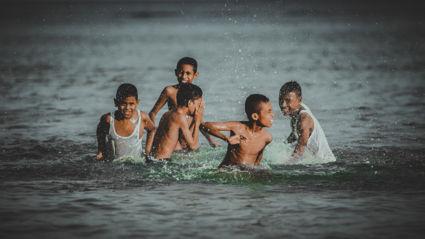 Kinderen in zee bij strand Natsepa, Suli Ambon