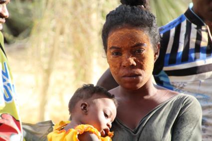 moeder met kind op strand Madagaskar (lege blik in ogen)